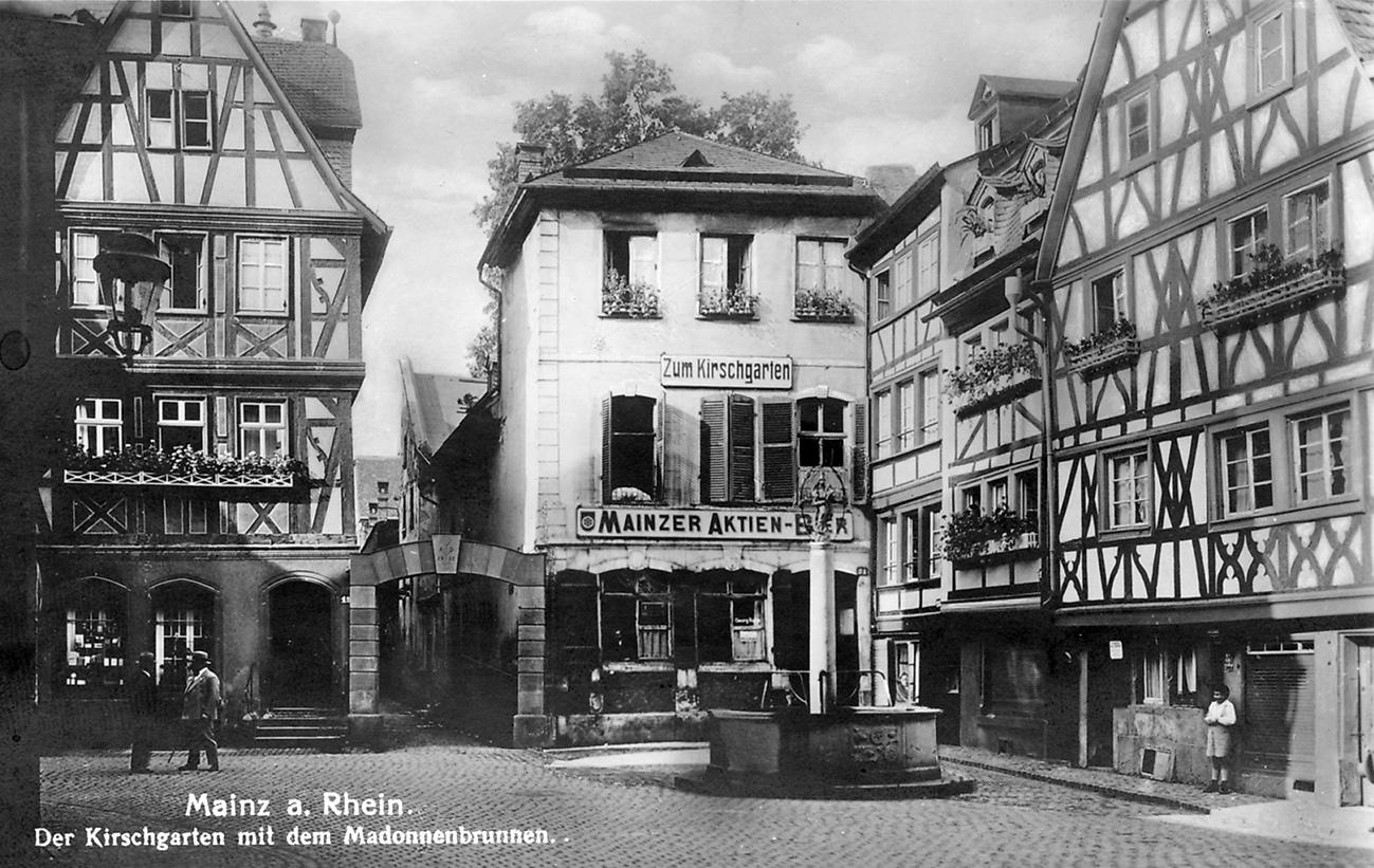 """""""Mainz a. Rhein. Der Kirschgarten mit dem Madonnenbrunnen"""" und der Gaststätte """"Zum Kirschgarten"""" (Kirschgarten 21), um 1932. Postkarte (Nr. 216). Verlag: Ludwig Feist, Mainz."""